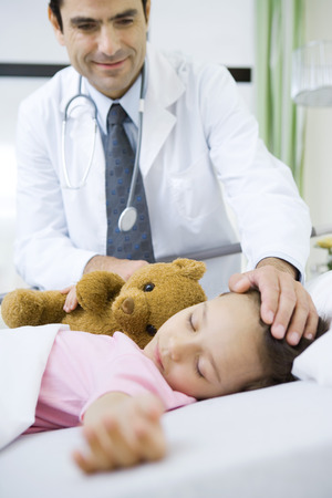 Doctor with hand on sleeping childs head, smiling