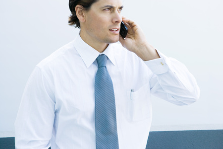 Young businessman using cell phone, waist up, cropped view LANG_EVOIMAGES