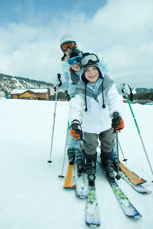Young skiers on snow, smiling at camera, full length, portrait