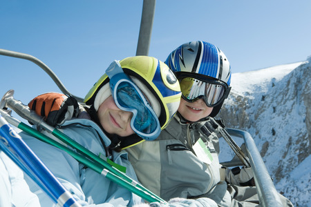 kids at the ski lift: Two young skiers on chair lift, smiling at camera together, portrait
