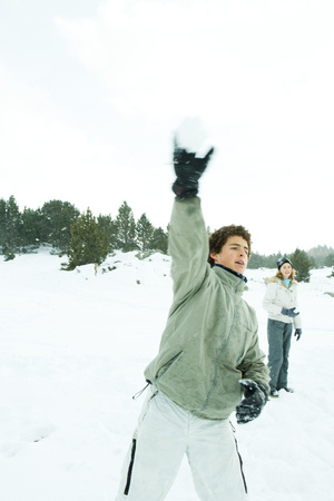 Teenage boy throwing snowball, blurred motion LANG_EVOIMAGES