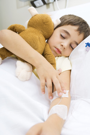 Boy lying in hospital bed, holding stuffed animal