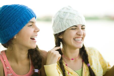 Young female friends wearing knit hats, laughing