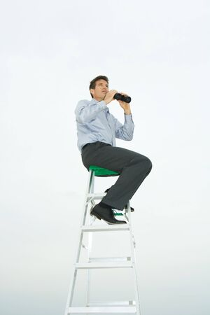 Man sitting on top of ladder, holding binoculars, looking up