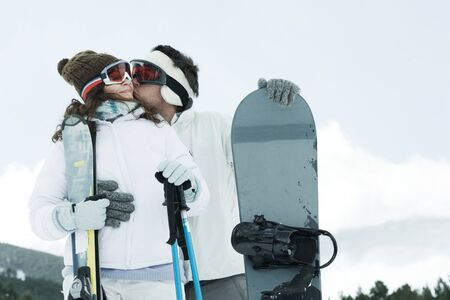 Young couple standing outside with skis and snowboard, man kissing girlfriends cheek LANG_EVOIMAGES