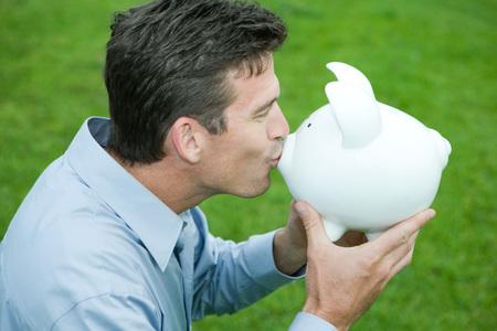 Man kissing piggy bank, side view