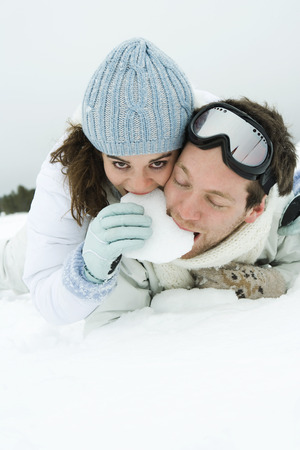 Young couple lying on the ground together, eating snow, female smiling at camera