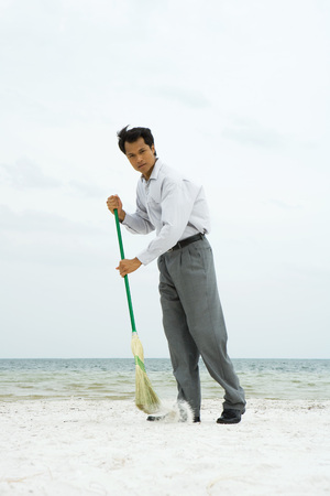 Man standing on beach sweeping with broom, looking at camera LANG_EVOIMAGES