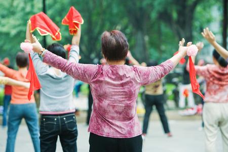 handkerchief: China, Guangzhou, women practicing tai chi chuan outdoors, rear view