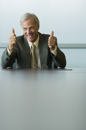 Businessman giving two thumbs up, smiling at camera