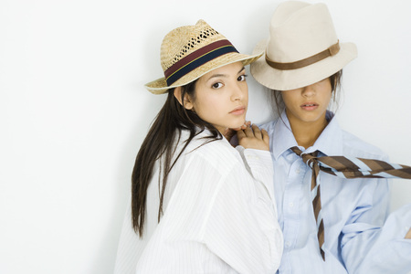 Two young females dressed in mens clothing, one looking at camera