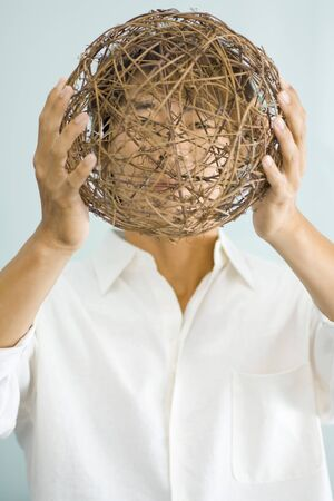 intertwined: Man holding sphere in front of face
