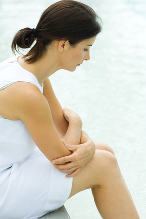 unease: Woman sitting with arms folded, head down, side view LANG_EVOIMAGES