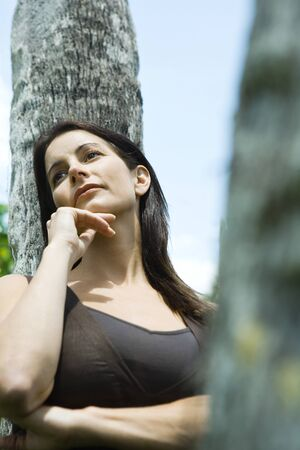 Woman leaning against tree trunk, hand under chin, low angle view LANG_EVOIMAGES