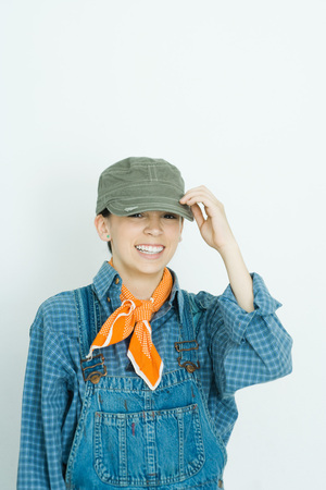 Teenage girl dressed in overalls, putting on hat, smiling at camera