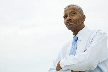 Businessman with arms folded, looking away, low angle view