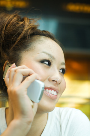 Young woman using cell phone, smiling, looking away, close-up