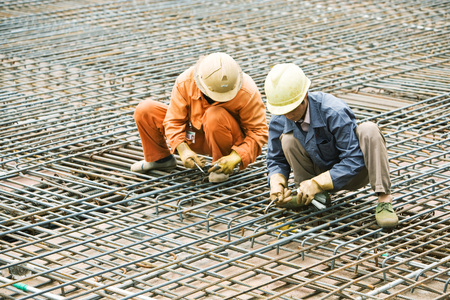 Construction workers crouching on steel framework, both looking down