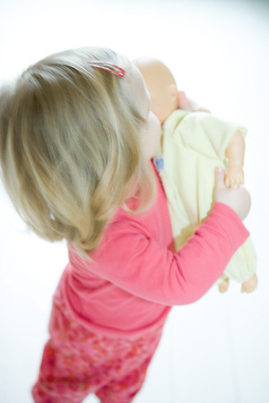 Blonde toddler girl holding baby doll LANG_EVOIMAGES