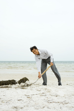 Man at the beach scooping sand with shovel, smiling at camera, full length