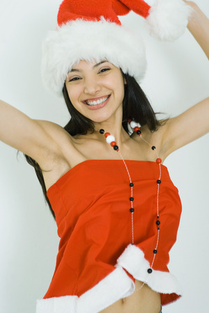 Teenage girl in Santa hat jumping with arms raised, smiling at camera LANG_EVOIMAGES