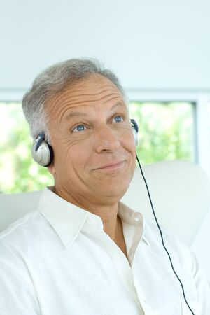 Mature man listening to headphones, smiling, looking up LANG_EVOIMAGES