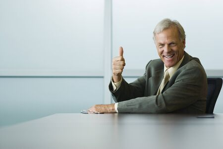 Businessman making thumbs up gesture and smiling at camera