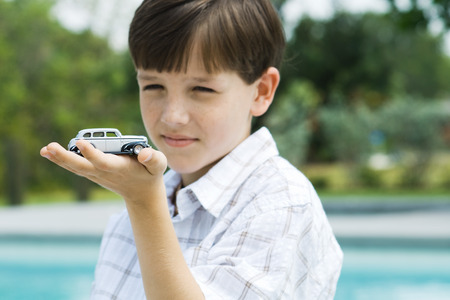 Boy holding toy car in palm of hand
