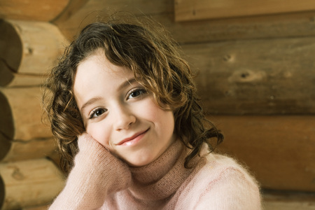 Girl leaning head on hand, smiling at camera