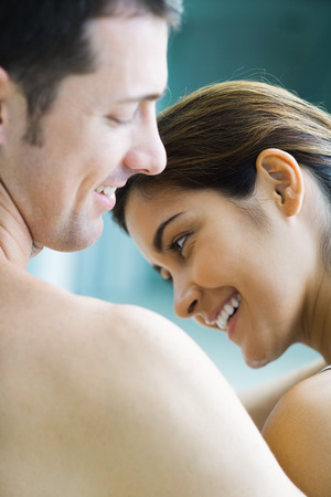 Couple smiling, womans head lowered, cropped view