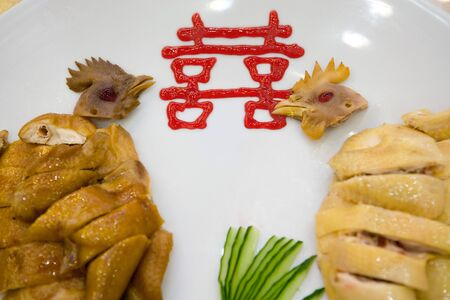 Close-up of cooked chickens on plate with Chinese ideogram