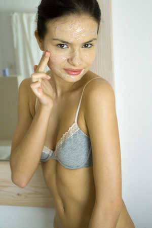 half naked: Young woman in underwear applying facial mask, looking at camera