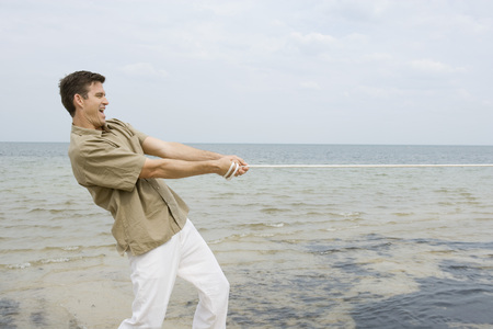 Man playing tug-of-war at the beach, side view