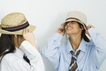 Two young female friends wearing mens clothing and putting on hats