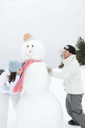 Young couple peeking around snowman at each other, holding up snowballs