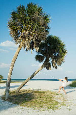 authoritative woman: Female at the beach, pulling rope tied to palm tree, mid-distance LANG_EVOIMAGES