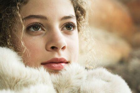 furs: Teen girl under soft blanket, close-up LANG_EVOIMAGES