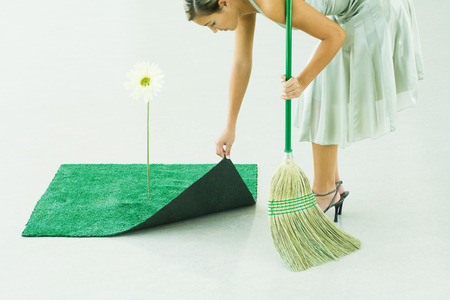 Woman bending over, broom in hand, lifting corner of artificial turf next to gerbera daisy LANG_EVOIMAGES