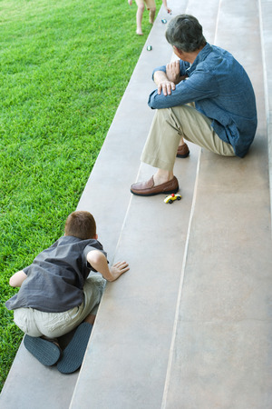 arrodillarse: Grandfather and grandchildren sitting on steps, playing with toy cars, high angle view LANG_EVOIMAGES
