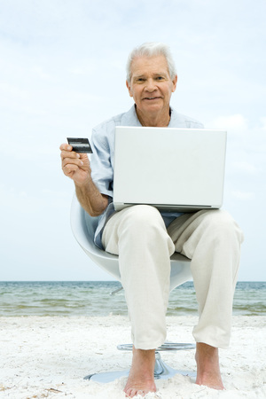 edge: Senior man using laptop on beach, making on-line purchase with credit card