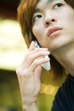 distractions: Young man using cell phone, looking up, close-up