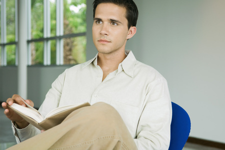 distractions: Man sitting in chair, holding book, looking away