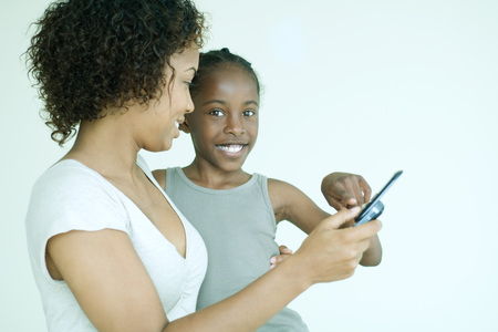 Mother showing daughter cell phone, daughter smiling at camera