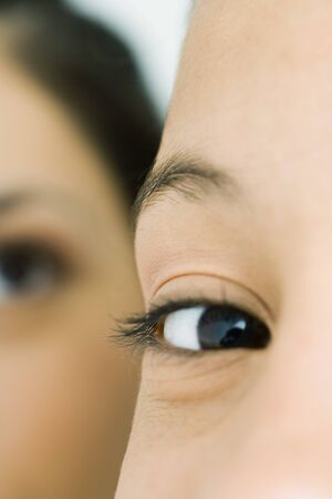 Teenage girl looking at camera, cropped view of eye