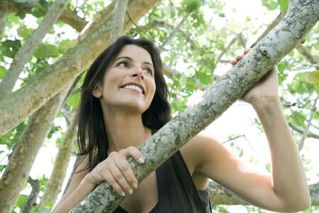 leaning against: Woman looking over branch, low angle view