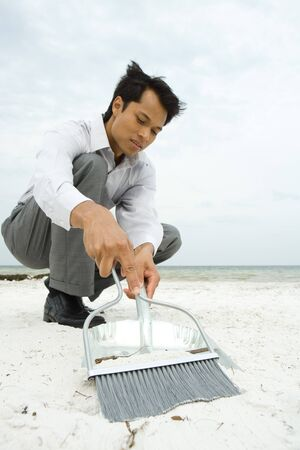 Man crouching on beach, sweeping sand into dustpan, low angle view