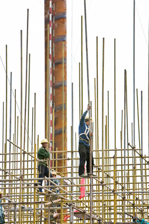 connecting rod: Construction workers on standing on scaffolding, low angle view LANG_EVOIMAGES