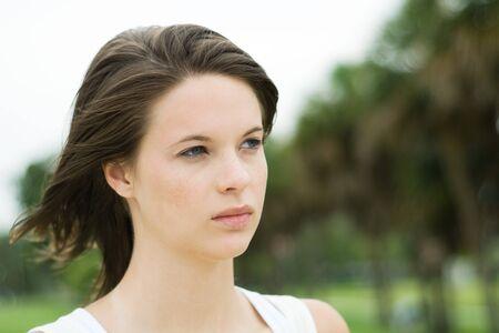 Teen girl looking away, hair blowing in wind, head and shoulders