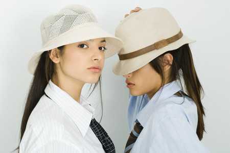 Two young female friends wearing hats, one looking at camera, the others eyes covered