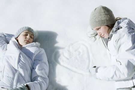 Teenage girls lying on snow, one drawing heart with initials in snow